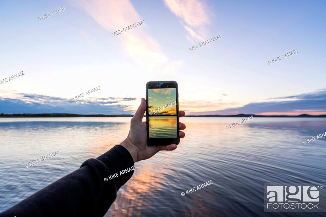 Photo de stock: Finland, Lapland, man taking cell phone picture of stunning lake at twilight.