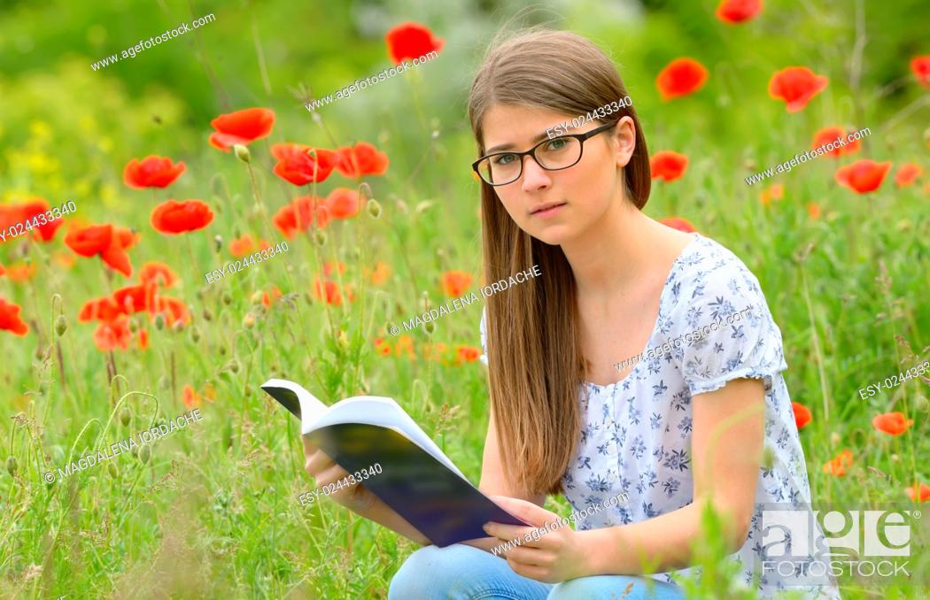 Photo de stock: Teen girl reading book in the poppies field.
