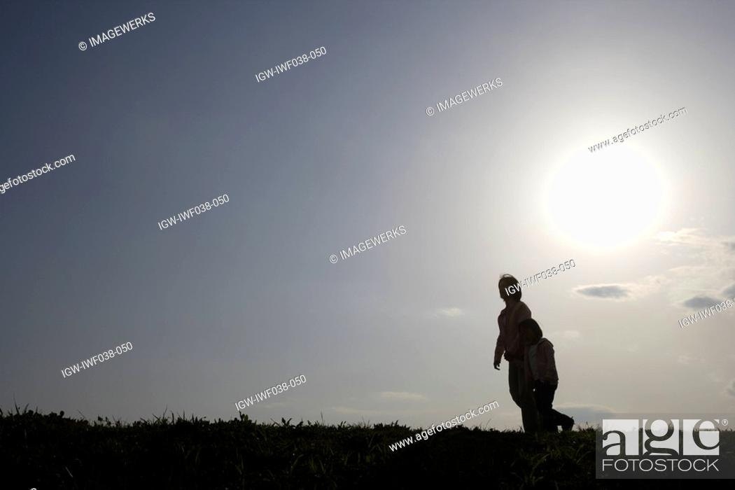 Stock Photo: Silhouette of a mother and daughter walking.