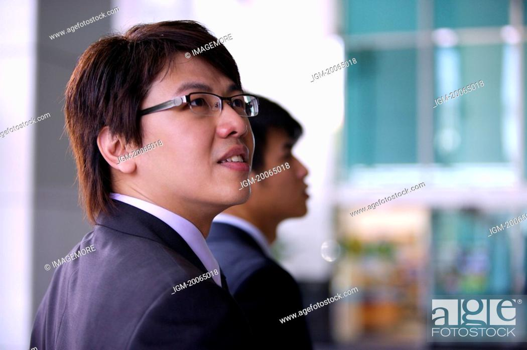 Stock Photo: Young man looking up with smile.