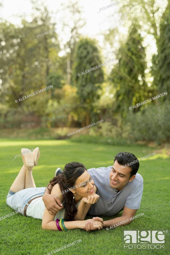 Stock Photo: Man with arm around woman lying on grass.