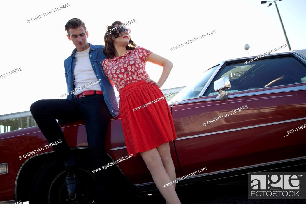 Stock Photo: A cool, rockabilly couple leaning against a vintage car.