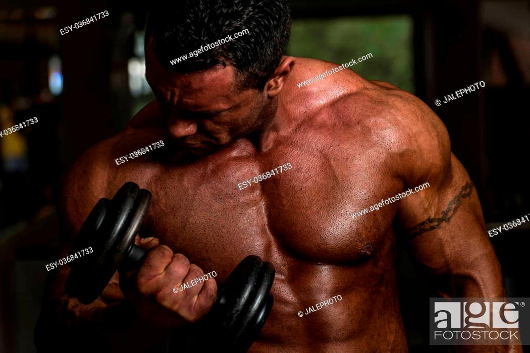 Stock Photo: bodybuilder doing heavy weight exercise for biceps with dumbbell.