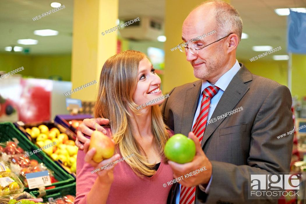 Stock Photo: Germany, Cologne, Man and woman with apple and pear in supermarket, smiling.