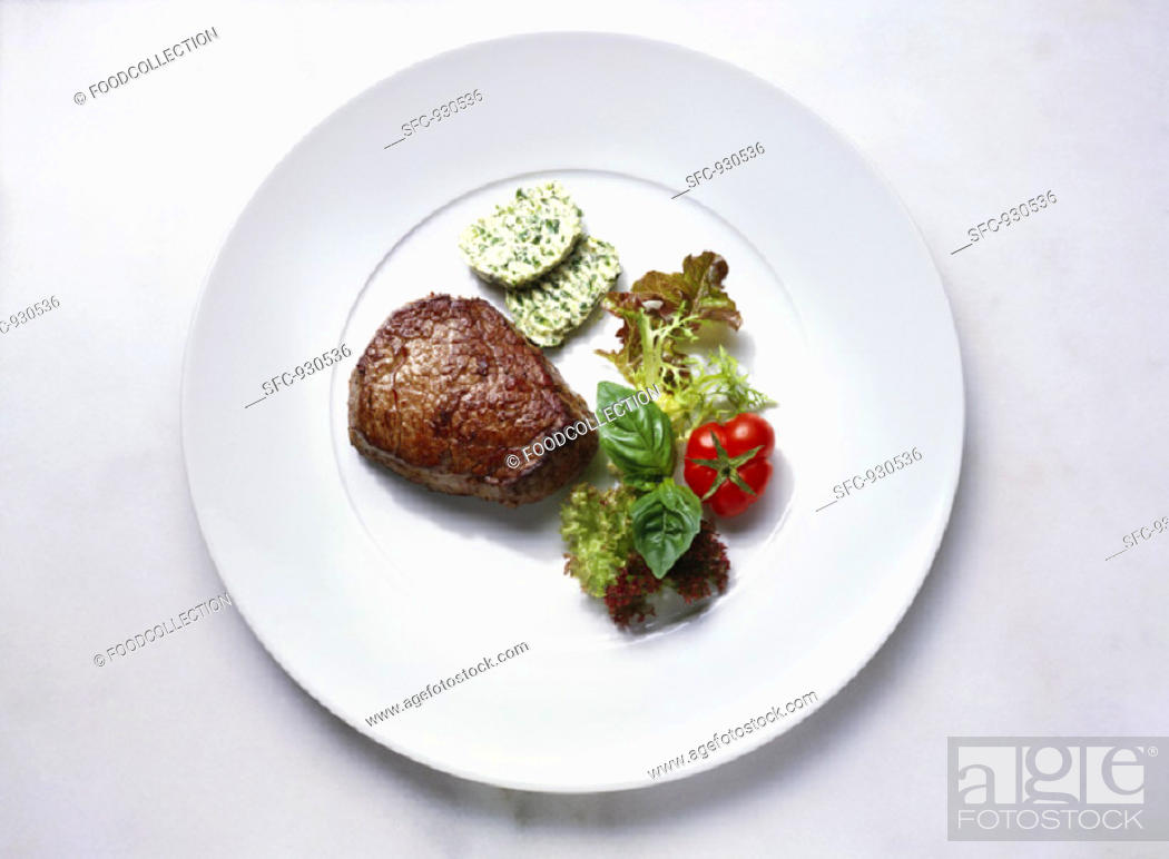 Stock Photo: Fillet steak with herb butter and salad.