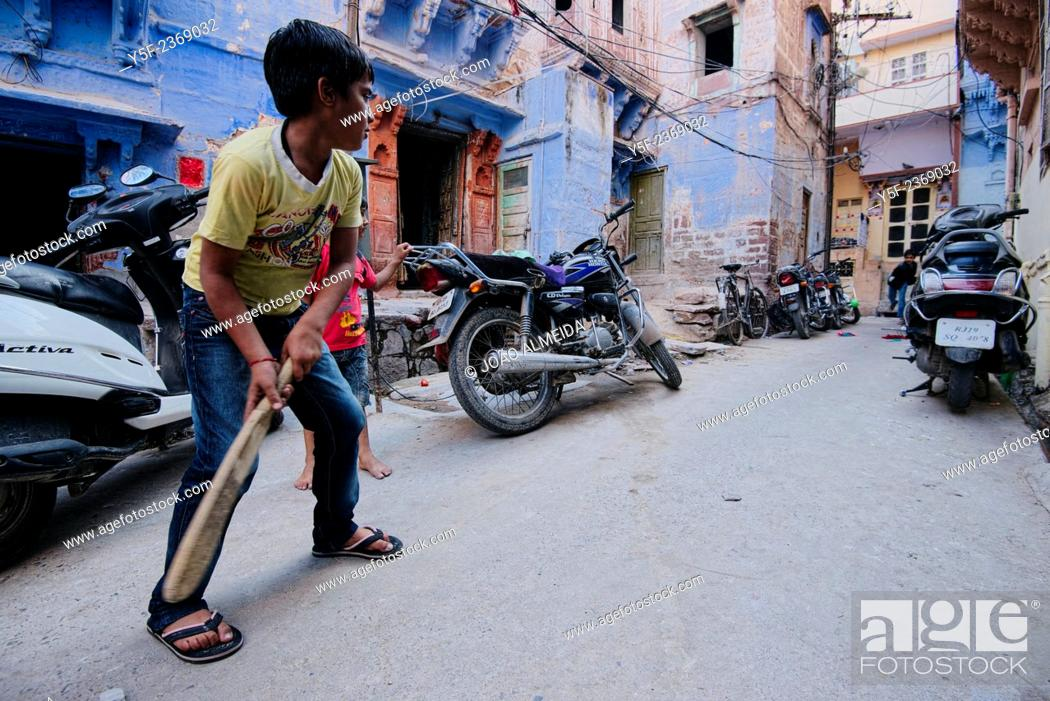 Stock Photo: Boys playing cricket on the street.