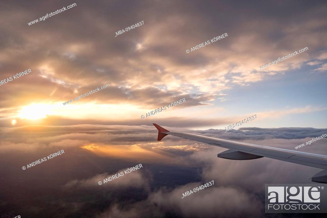 Photo de stock: View from the window of an airplane at sunset on opening cloud cover and mainland.