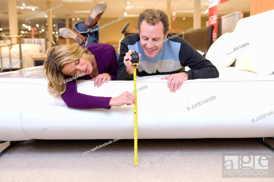 Stock Photo: Young couple measuring bed in furniture shop.
