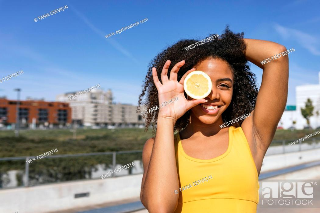 Stock Photo: Portrait of laughing young woman covering eye with lemon half.