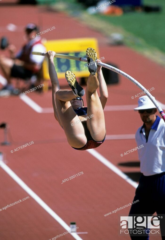 Stock Photo: Female pole vaulter bends bar as she attempts a clearance watched closely by judge at track.