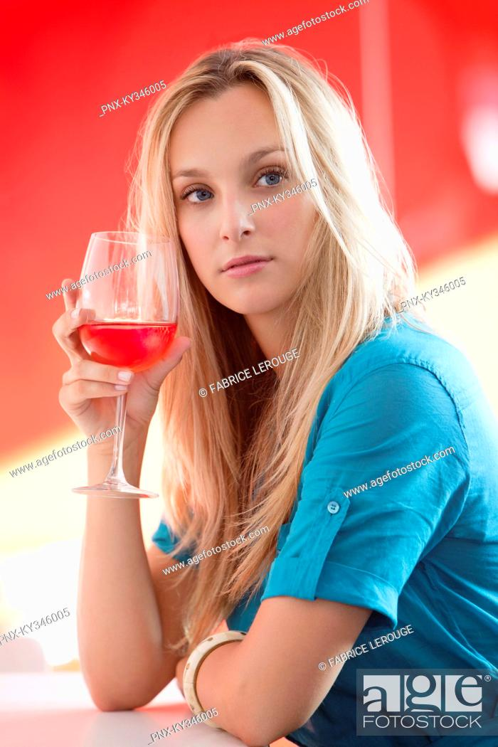 Stock Photo: Young woman having red wine and thinking in a bar.
