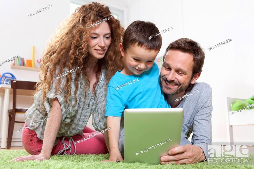 Stock Photo: Germany, Berlin, Family using digital tablet on floor.