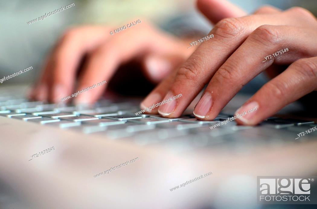 Stock Photo: Young woman types on a pink laptop.