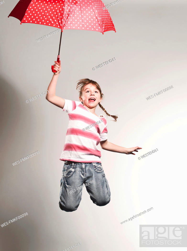 Stock Photo: Girl 6-7 jumping with holding umbrella.