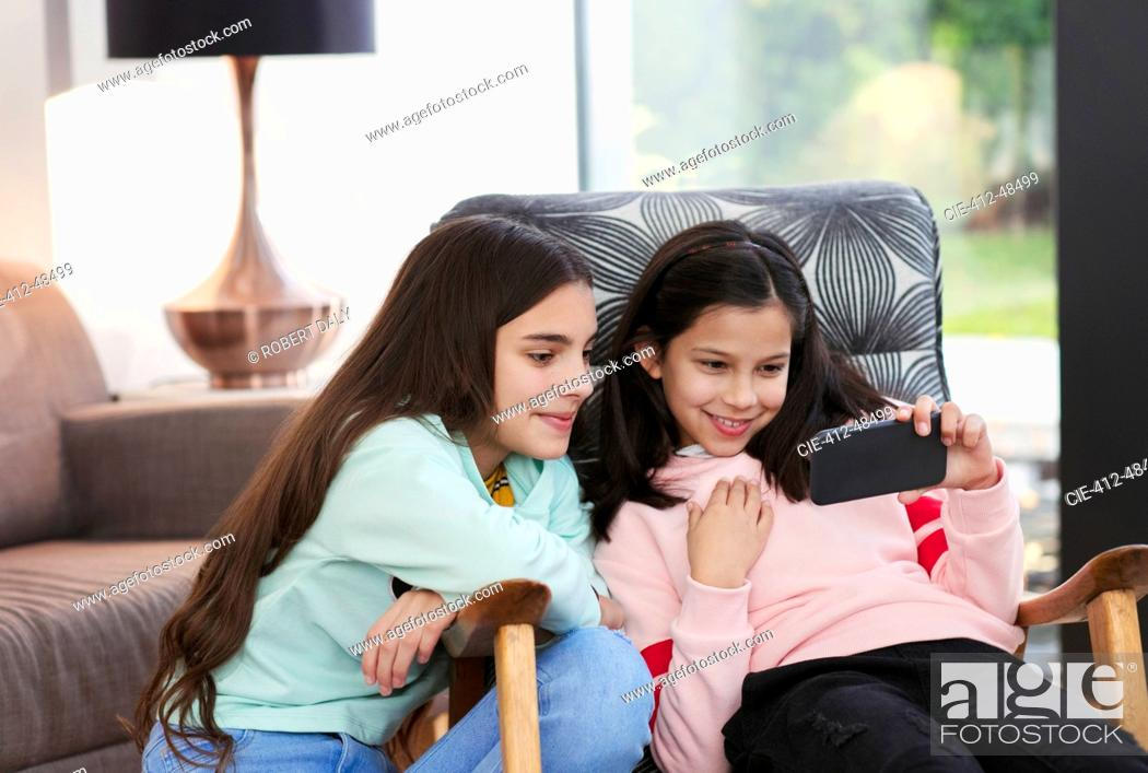 Stock Photo: Sisters using smart phone in living room.