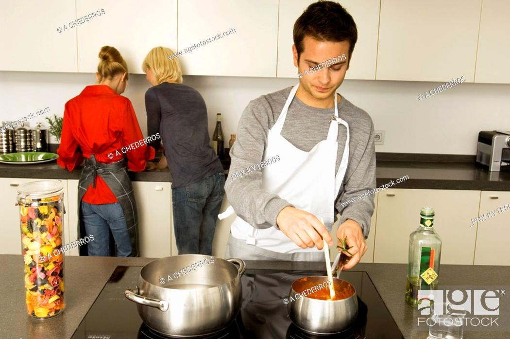 Stock Photo: Young man cooking food with two young women standing behind him.