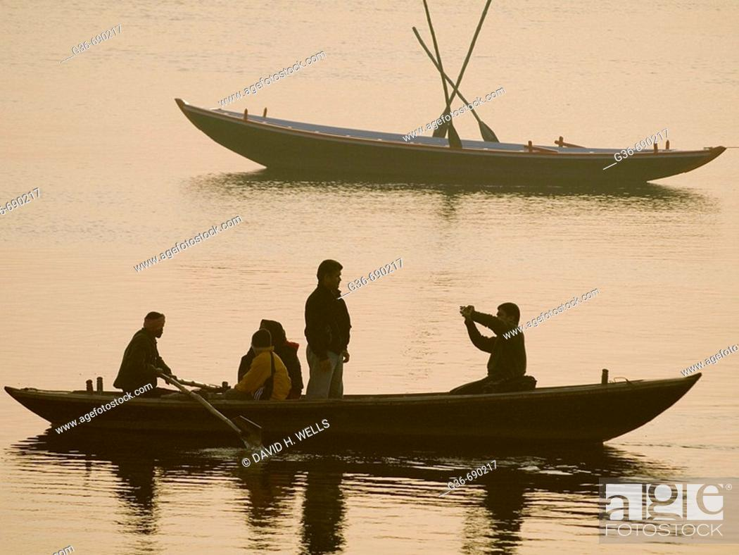 Stock Photo: Boats with pilgrims and tourists at dawn in Varanasi, India, a sacred Hindu pilgrimage site.