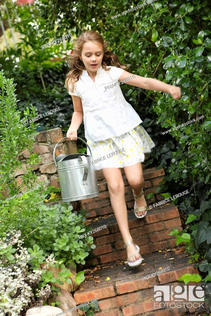 Stock Photo: Girl running with a watering can.