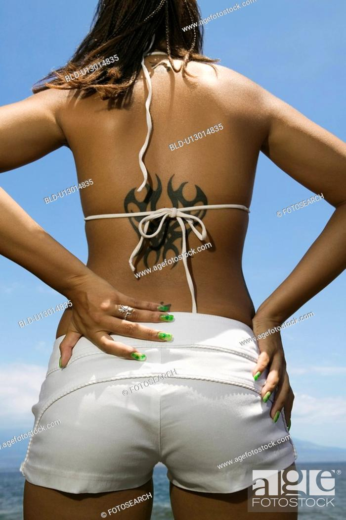 Stock Photo: Rear view of multi ethnic young adult woman on beach with hands on hips and tattoo.