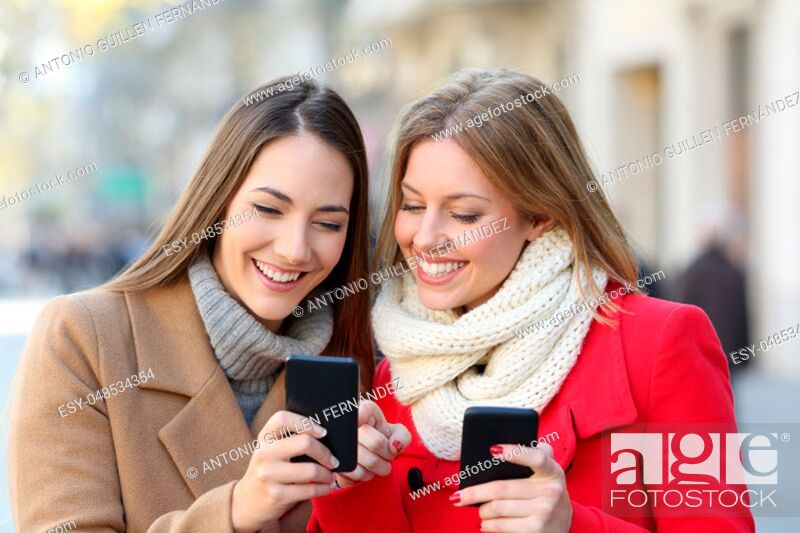 Stock Photo: Friends consulting smart phone content in the street in winter.