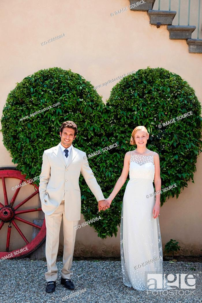 Stock Photo: Newlyweds by heart shaped bush holding hands.