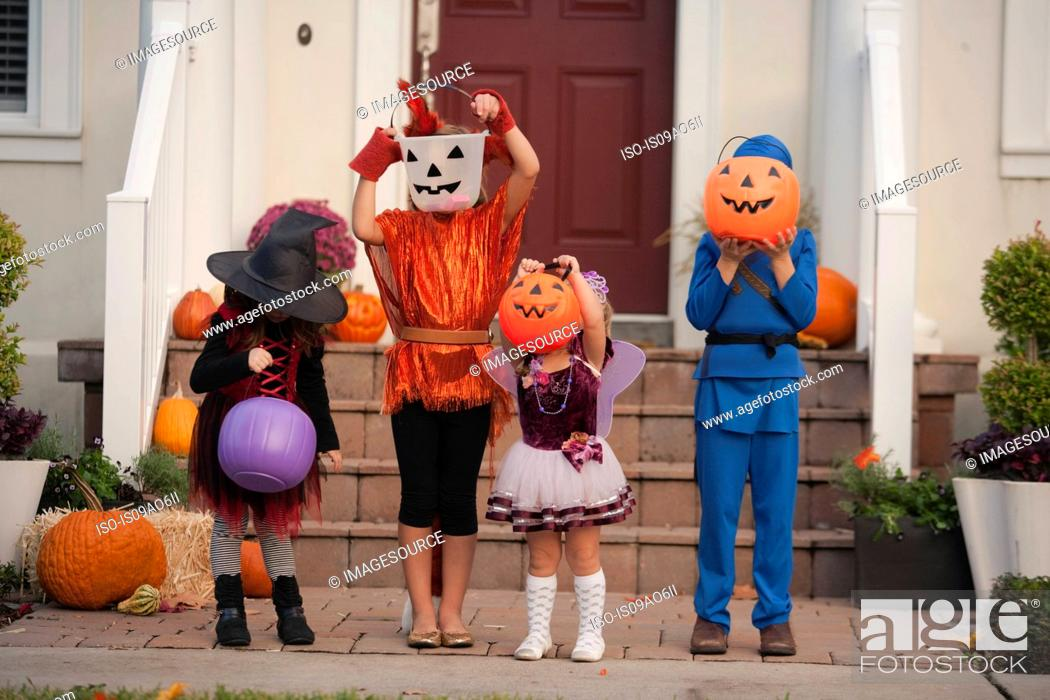 Stock Photo: Children covering face with Jack O' Lantern bucket in front of house.
