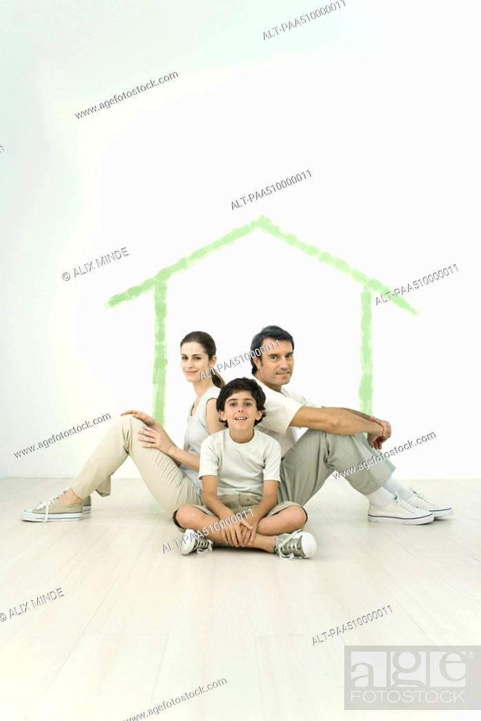 Stock Photo: Family sitting back to back in front of outline of house painted on wall.