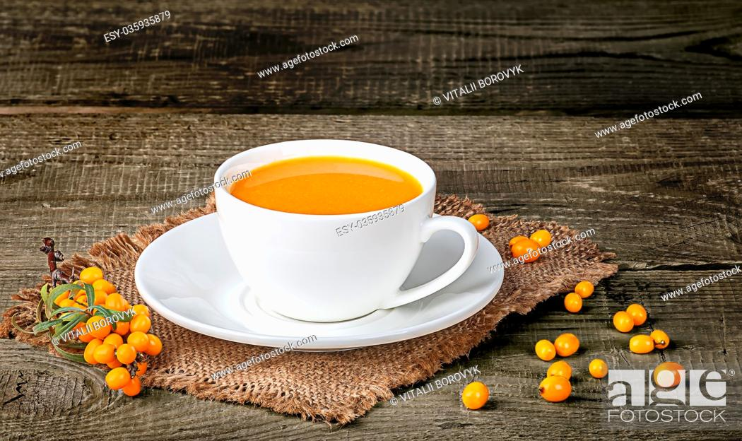 Stock Photo: Tea of sea-buckthorn berries on wooden table with blurred background.