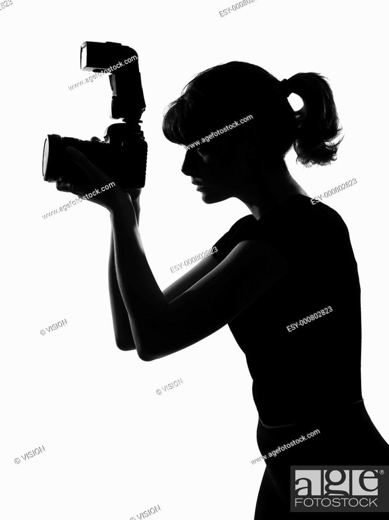 Stock Photo: portrait silhouette in shadow of a young woman photographer holding a camera in studio on white background isolated.