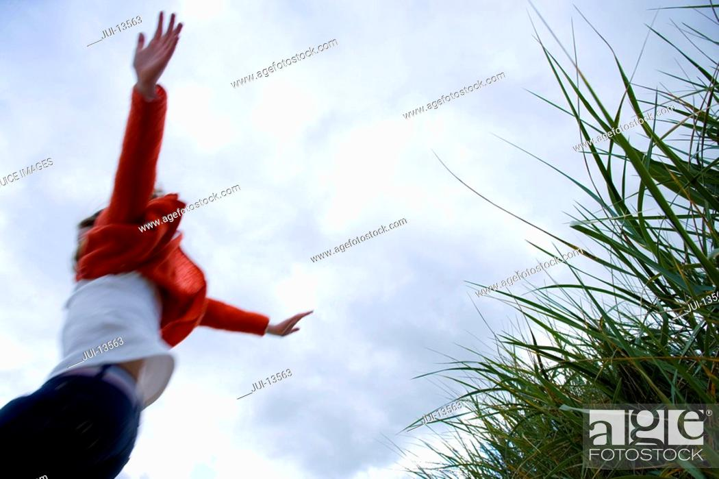 Stock Photo: Girl 7-9 years jumping from grass outdoors, low angle view.