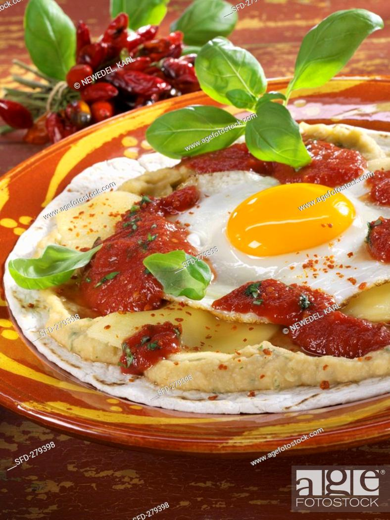 Stock Photo: Tortilla with bean puree, cheese, tomato sauce & fried egg.