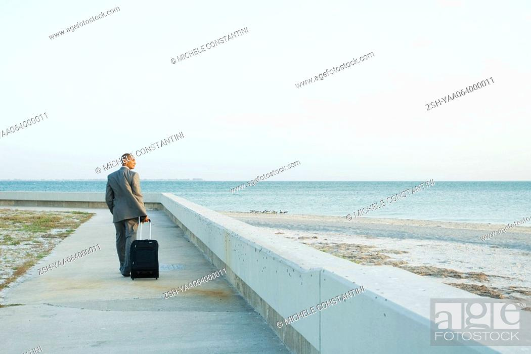 Stock Photo: Businessman walking on sidewalk at the beach, pulling suitcase behind him, looking at view.