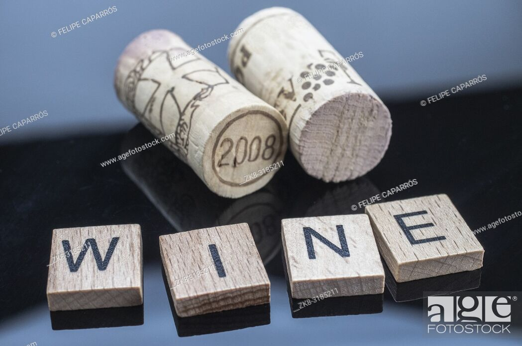 Stock Photo: Two corks next to a few letters of wood with the word wine.