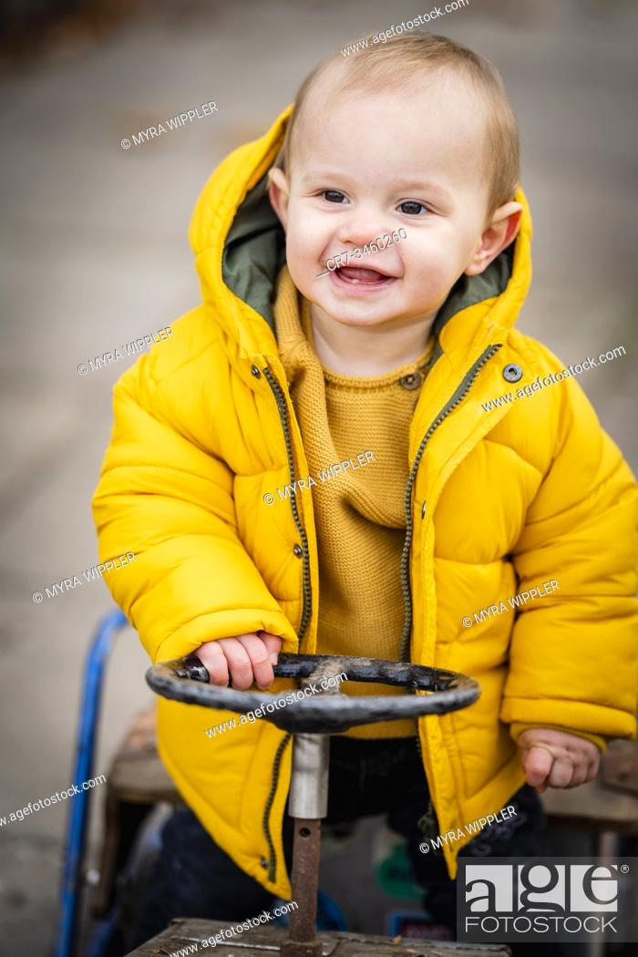 Imagen: Baby boy of one year old driving a play toy cart and having fun.