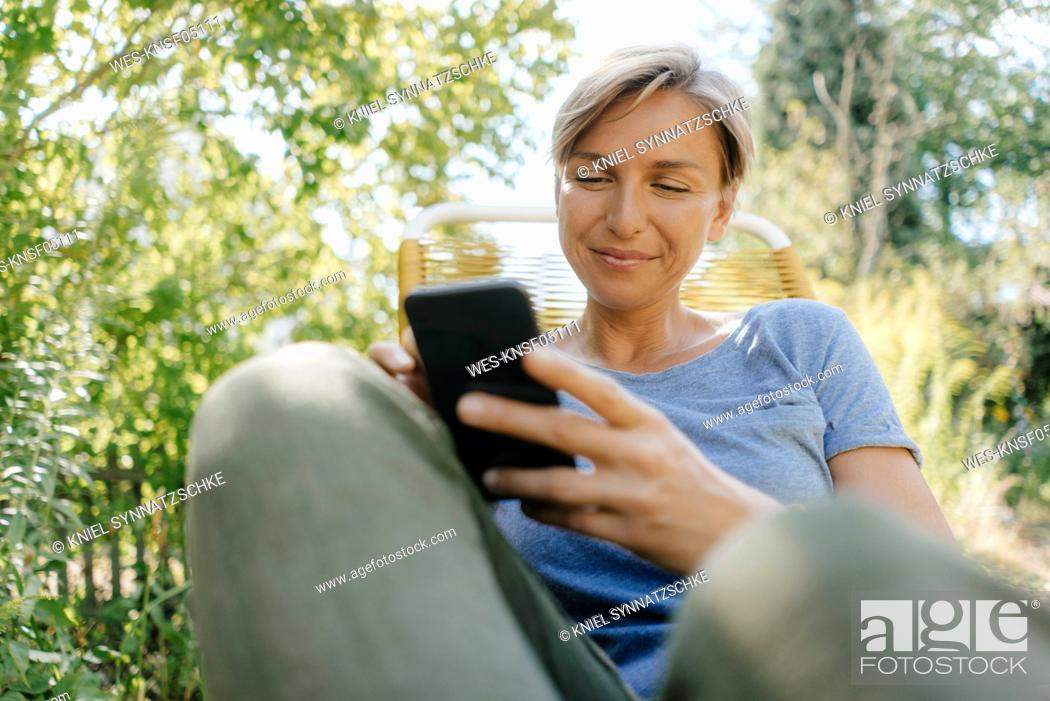 Stock Photo: Woman sitting in garden on chair using cell phone.