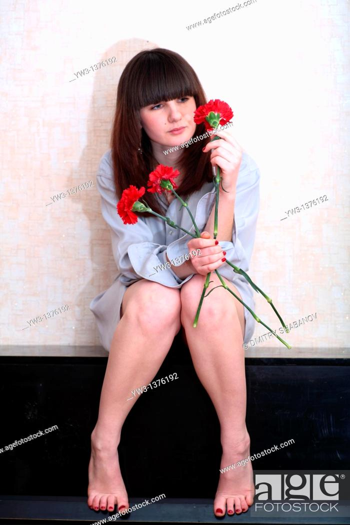 Stock Photo: Pretty brunette woman indoors with flowers.