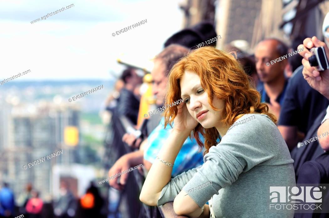 Imagen: Sad girl among tourists on Eiffel Tower  Loneliness, misunderstanding.