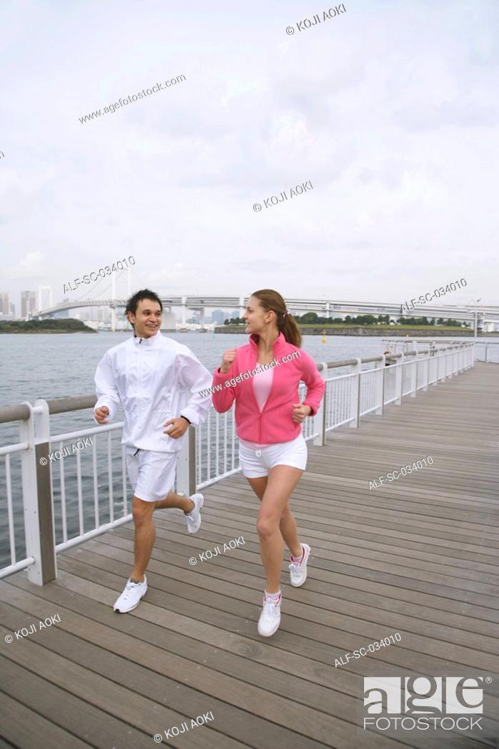 Stock Photo: Young couple jogging on bridge.