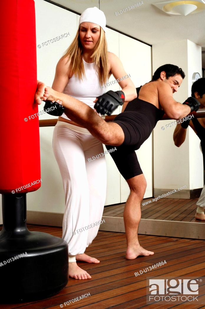 Stock Photo: Young man and woman hitting the punching bag.