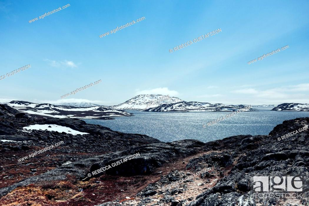 Stock Photo: Scenic view of snow covered landscape and sea against blue sky.