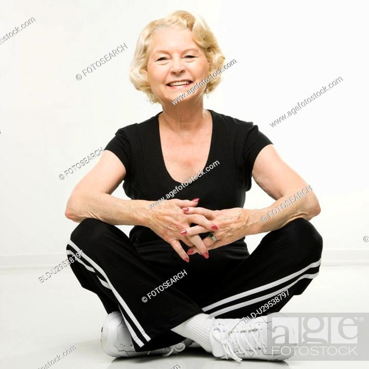 Stock Photo: Woman sitting on floor with legs crossed.