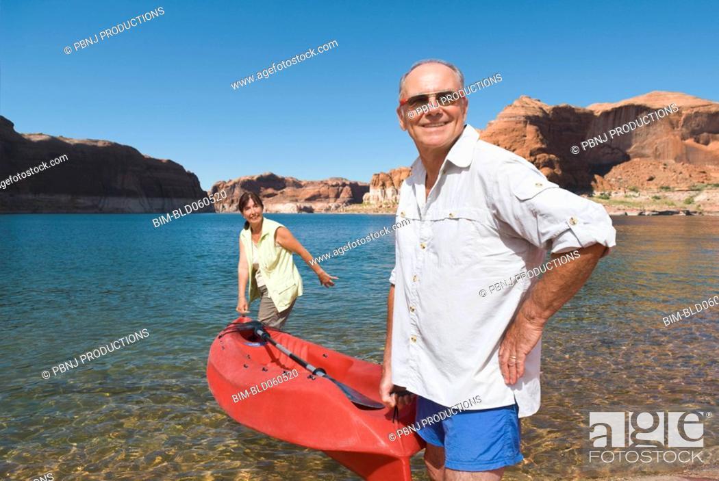 Stock Photo: Multi-ethnic senior couple carrying kayak.