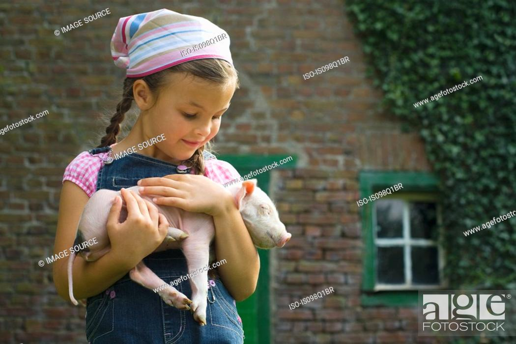 Stock Photo: A girl holding a piglet.