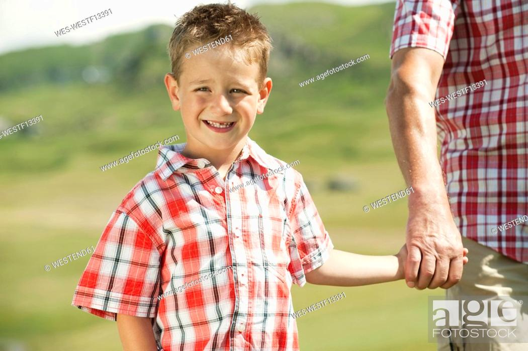 Stock Photo: Italy, Seiseralm, Grandfather and grandson 6-7 hand in hand, smiling, portrait, close-up.