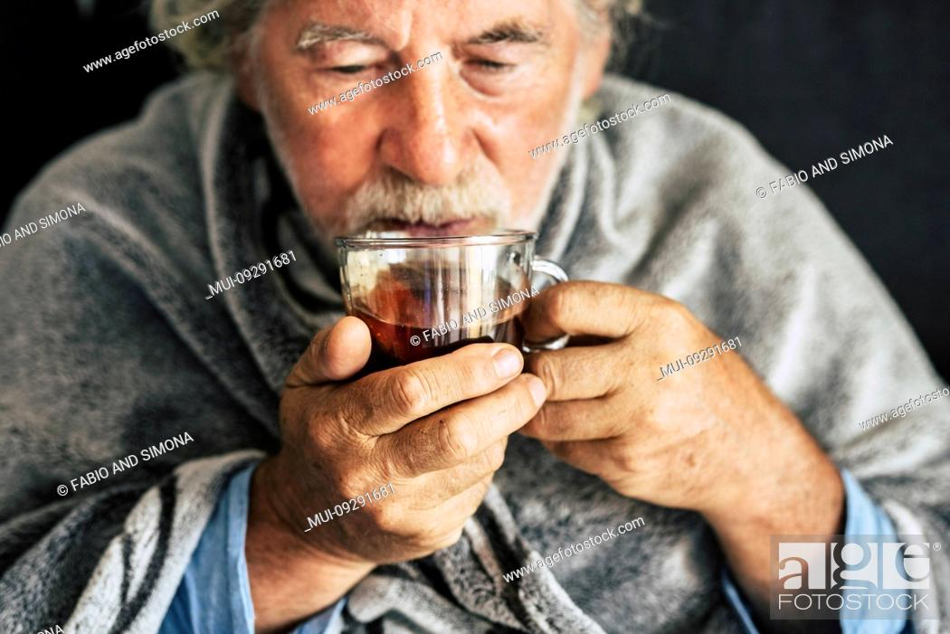 Stock Photo: Old people senior man with winter seasonal illness fever cold problems drinking a pharmacy medicine or hot tea to go healthy - concept of mature retired with.
