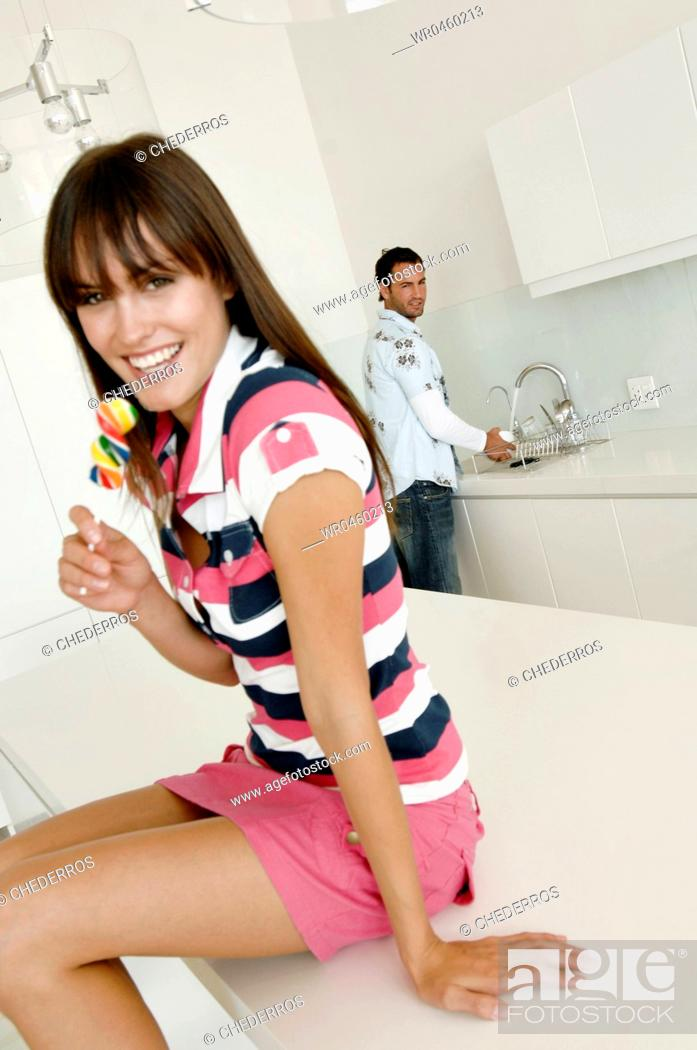 Stock Photo: Portrait of a young woman sitting on a kitchen counter and holding a lollipop.