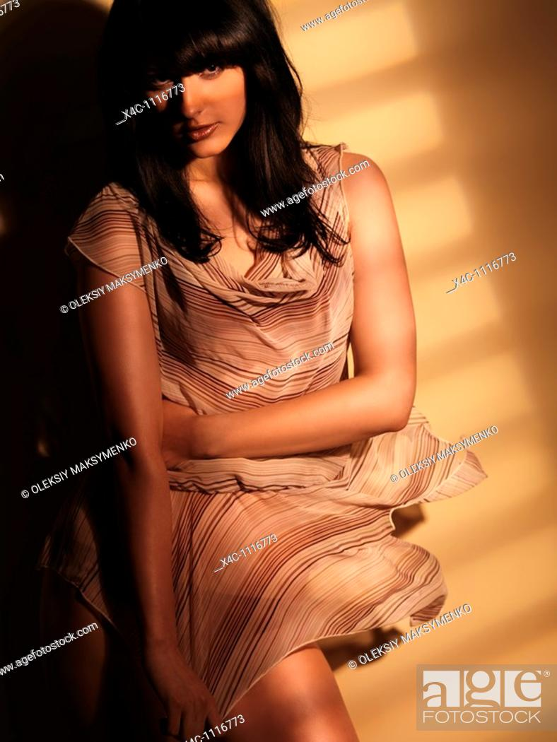 Stock Photo: Beautiful young woman in light flying dress standing in light coming through a window  Artistic dynamic fashion photo.