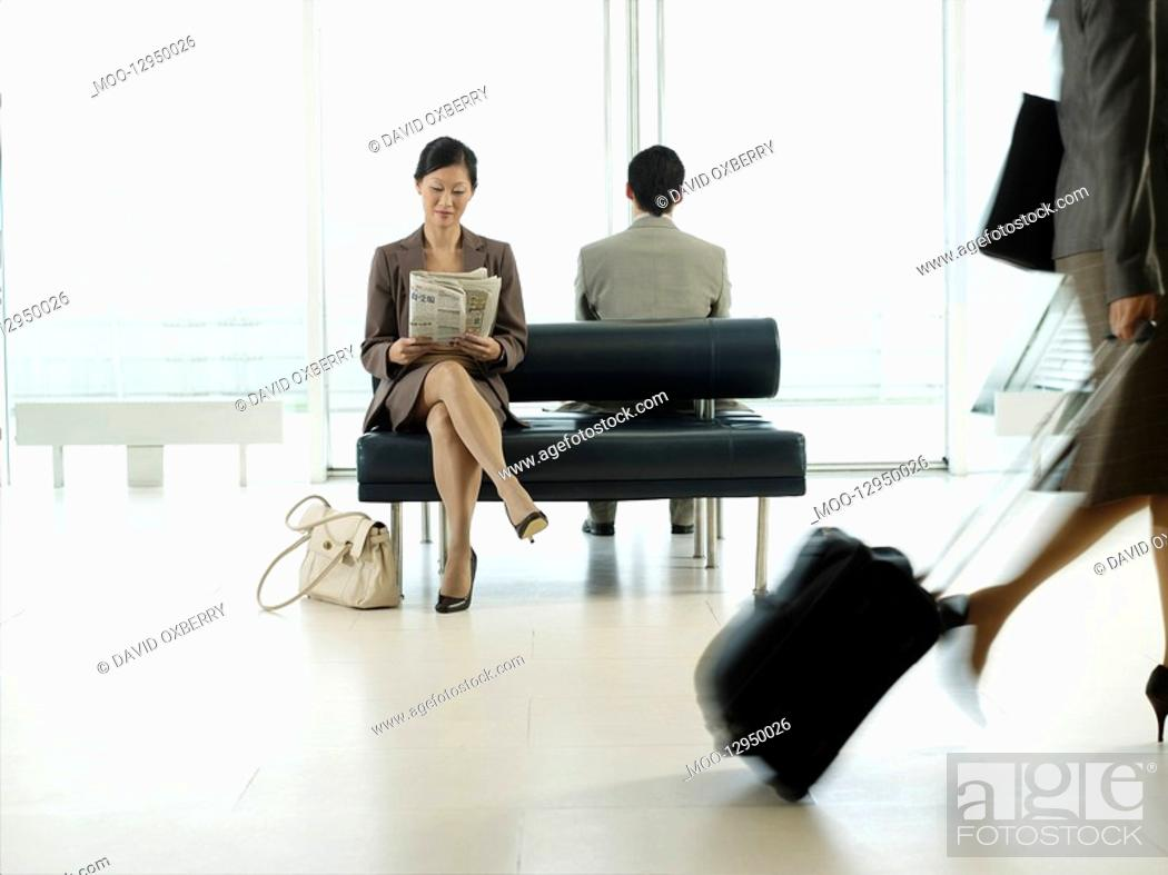 Stock Photo: Businesswoman sitting on bench in airport reading newspaper.