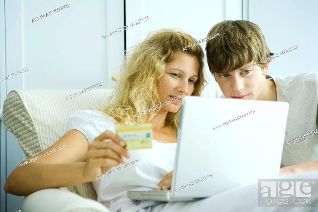 Stock Photo: Woman and teenage son making credit card purchase online.