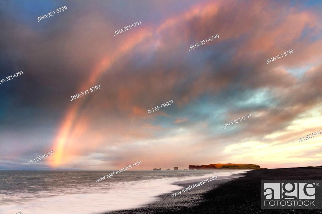 Stock Photo: Distant view of Dyrholaey at sunrise with rainbow, from Halsanefs Hellir Beach near Vik, South Iceland, Polar Regions.